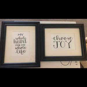 Two hand lettered signs in black frames